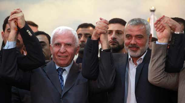Head of the Hamas government Ismail Haniyeh (right) and senior Fatah official Azzam Al-Ahmed (left) raise their hands together at a news conference that announced a unity agreement between the rival Palestinian factions in Gaza City on April 23, 2014. Credit: Abed Rahim Khatib/Flash90.