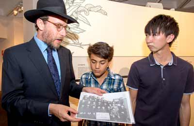 Rabbi Levi Wolff shows Asher Grynberg and Keisuke Sugihara his grandfather's photograph at the Sydney Jewish Museum