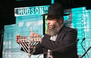 Rabbi Mendel Kastel lights the Menorah