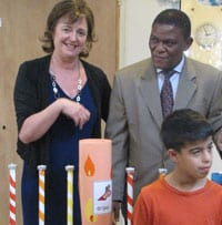 Ambassador Sis Ngmonbane and BIS executive director Jean Judes light the menorah with Yoav, a child with intellectual disabilities