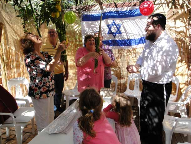 Rabbi Eli Feldman helps with the lulav and etrog