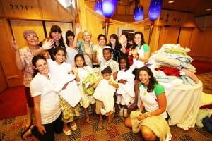 Sandy Sher [Back 3rd L] with Maccabiah team members, children from the home...and the towels [Photo Maccabiah Media - Peter Haskin]