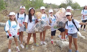 Alma Kalifa, Uri Shohat and Inbal Ben Ami clean with their friends. Photo: Yoav Devir