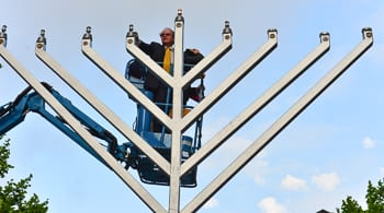 David Clarke lights the Menorah