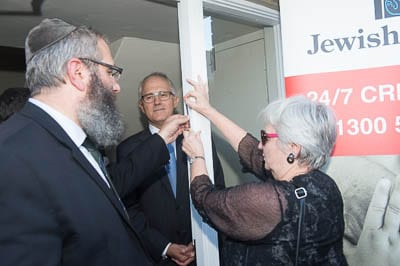Norah Goodridge attaches the mezuzah watched by Rabbi Kastel and Malcolm Turnbull