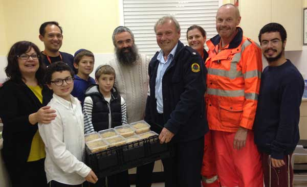 Shlomie Slavin [white shirt] and his family present food to SES chief Peter Gray [in dark jacket]