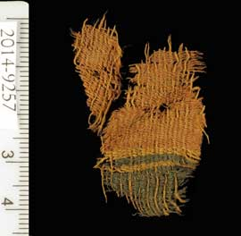 Fine wool textile dyed red and blue. The textile used the varying colors of natural animal hair to create black and orange-brown colors for decorative bands.   Clara Amit, courtesy of the Israel Antiquities Authority