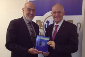 Professor Tim McCormack presenting the only known hard copy of the Turkel II Report in Australia to ECAJ ED Peter Wertheim