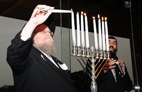 Rabbi Pinchus Feldman lights the Menorah